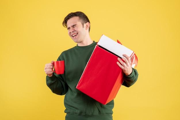 Вид спереди счастливый человек с зеленым свитером, держащий большой подарок и красную чашку, стоящий на желтом