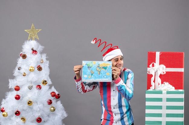 両手で地図を保持しているスパイラルスプリングサンタ帽子を持つ正面図幸せな男