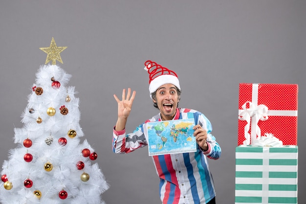 Front view happy man with spiral spring santa hat showing four fingers up