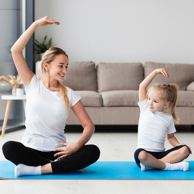 Front view of happy mother exercising with daughter at home