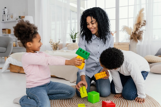 Vista frontale della madre felice che gioca in casa con i suoi figli