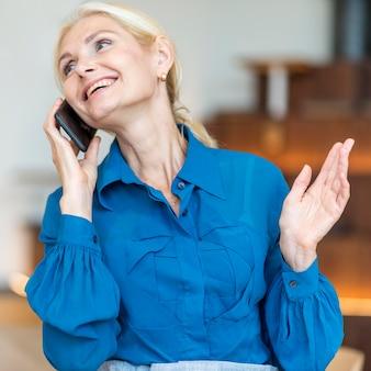 Vista frontale della donna anziana felice che parla al telefono mentre si lavora