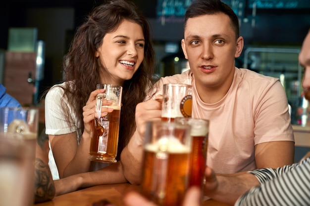 Front view of happy pair sitting together in pub, drinking beer and talking with friends. pretty woman and man enjoying rest, laughing and joking in cafe. concept of leisure and fun.