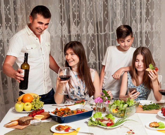 Front view of happy parents and children at dinner table