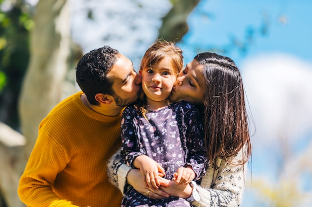 Front view of happy parents kissing her lovely daughter outdoors in the park in a sunny day