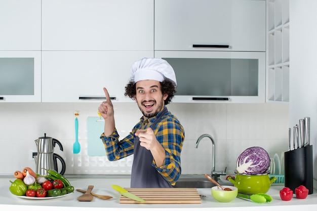 Vista frontale dello chef maschio felice e positivo con verdure fresche e cucina con utensili da cucina e puntando in avanti e in alto nella cucina bianca