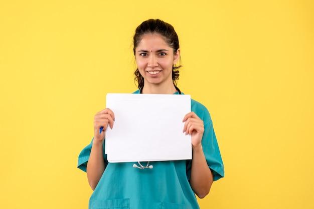 Medico femminile grazioso felice di vista frontale che tiene i documenti con entrambe le mani su fondo giallo