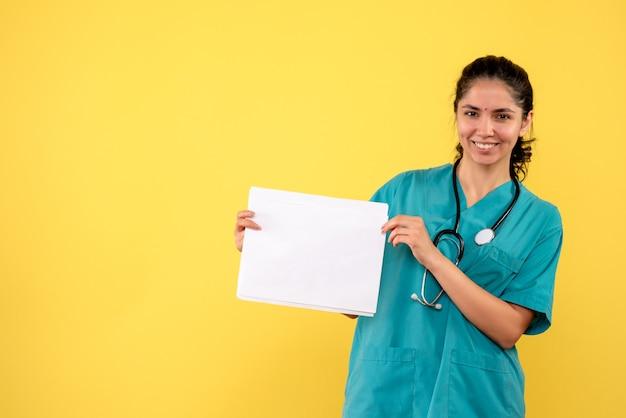 Medico femminile grazioso felice di vista frontale che tiene i documenti su fondo giallo