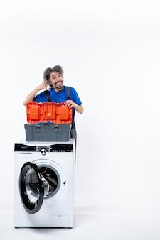 전면 보기 행복한 수리공이 흰색 공간에 있는 세탁기 뒤에서 저에게 전화를 걸어요