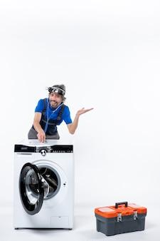 白いスペースの洗濯機に聴診器を置くヘッドランプと正面図幸せな修理工