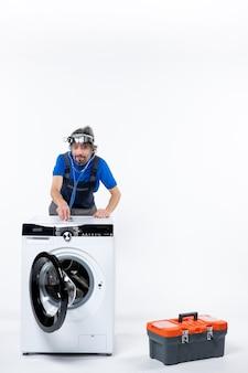 헤드 램프가 있는 전면 보기 행복한 수리공이 흰색 공간에 세탁기에 청진기를 얹고 있습니다.