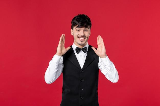 Vista frontale del cameriere maschio soddisfatto felice in un'uniforme con la farfalla sul collo su fondo rosso
