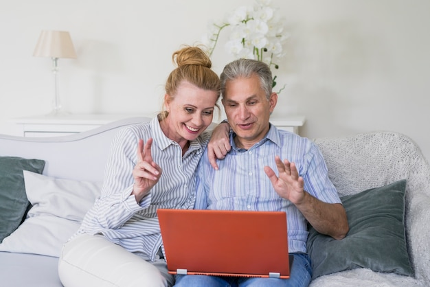 Front view happy senior couple with laptop