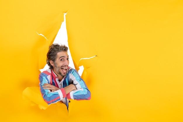 Vista frontale di un giovane ragazzo sorridente e ambizioso che posa per la macchina fotografica attraverso un buco strappato in carta gialla