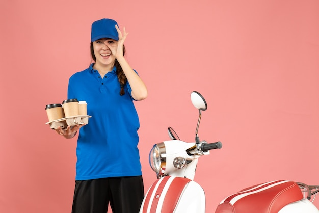 Front view of happy smiling courier girl standing next to motorcycle holding coffee and small cakes on pastel peach color background