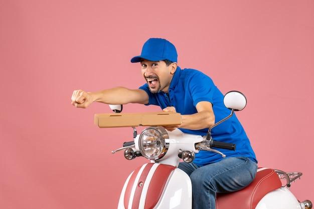 Vista frontale di un corriere sorridente felice che indossa un cappello seduto su uno scooter che tiene l'ordine su sfondo color pesca pastello