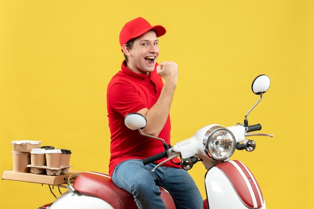 Front view of happy smiling young guy wearing red blouse and hat delivering orders on yellow background