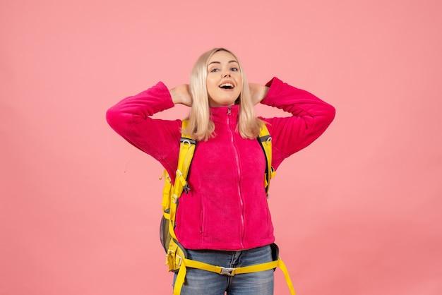 Вид спереди счастливая путешественница женщина в повседневной одежде, стоящая на розовой стене