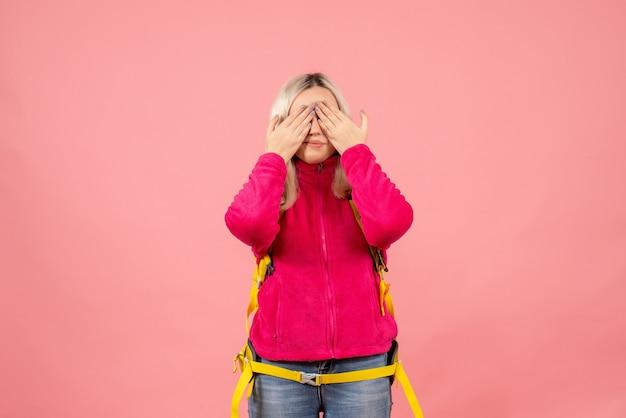Вид спереди счастливая путешественница женщина в повседневной одежде в рюкзаке, прикрывая глаза руками