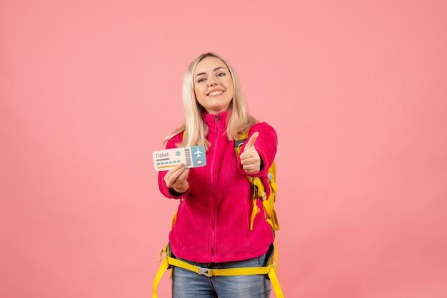 Вид спереди счастливая путешественница женщина в повседневной одежде в рюкзаке держит билет, делая большой палец вверх знак