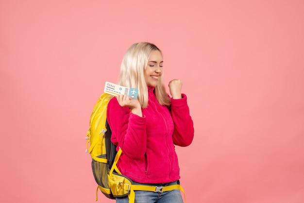Вид спереди счастливая путешественница женщина в повседневной одежде в рюкзаке с билетом