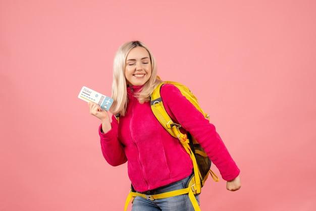 旅行チケットを保持しているバックパックを身に着けているカジュアルな服を着た幸せな旅行者の女性の正面図