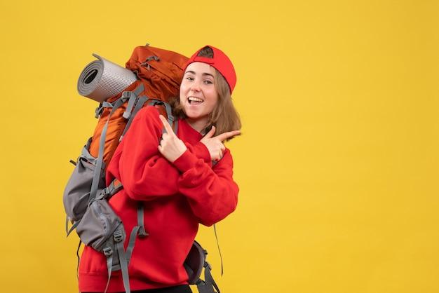 Вид спереди счастливая путешественница женщина в красном рюкзаке, скрещивая руки