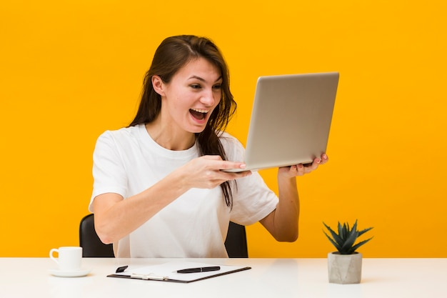 Front view happy woman at desk holding up laptop