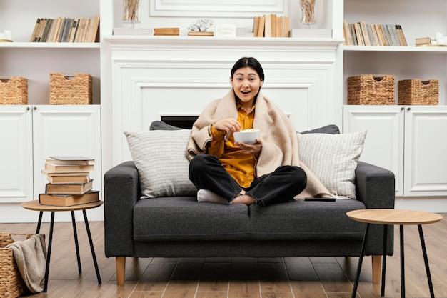 Вид спереди счастливая женщина ест попкорн и сидит на диване