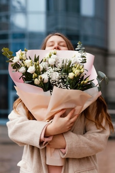 Front view of happy woman holding bouquet of flowers in the city