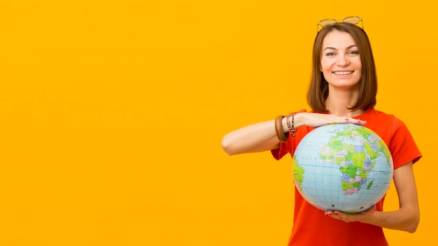 Front view of happy woman holding globe with copy space