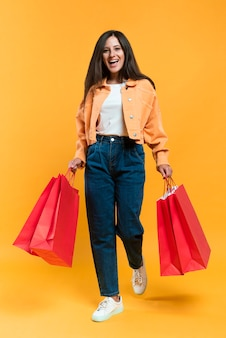 Front view of happy woman holding shopping bags