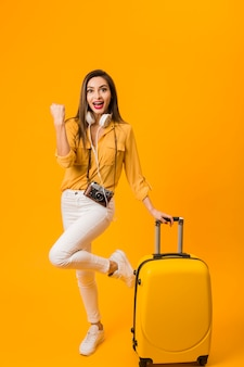 Front view of happy woman next to luggage