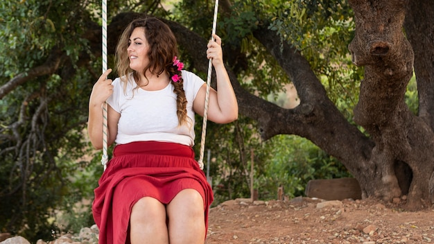 Front view of happy woman outdoors in swing