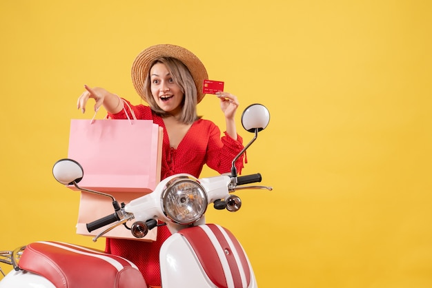 Front view of happy woman in red dress on moped holding shopping bags and card pointing at something