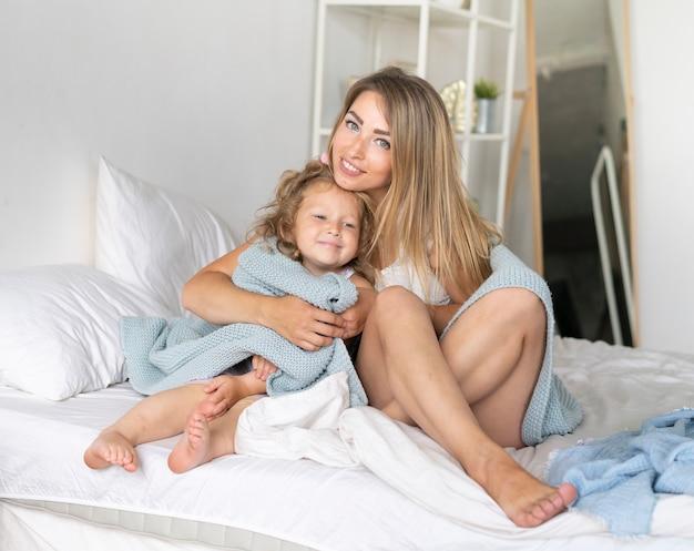 ベッドで娘と一緒に座っている正面幸せな女