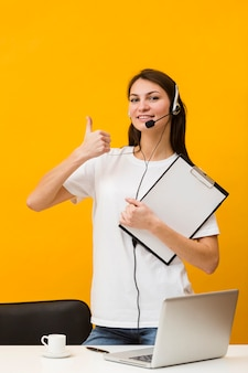 Front view of happy woman wearing headset and giving thumbs up