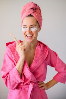 Vista frontale della donna felice con le bende sull'occhio