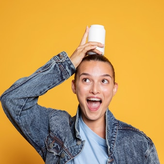 Front view of happy woman with soda can on her head