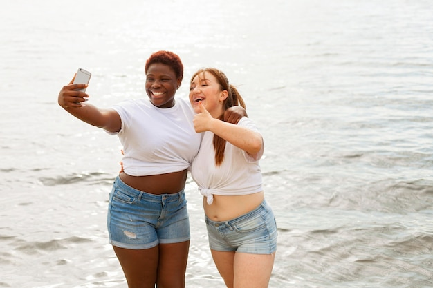Front view of happy women taking selfie at the beach