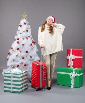 흰색 크리스마스 트리 근처 서 산타 모자를 쓰고 전면보기 행복 한 크리스마스 소녀