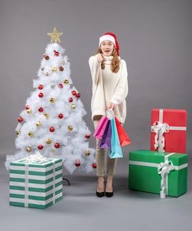 カラフルな買い物袋と正面図幸せなクリスマスの女の子