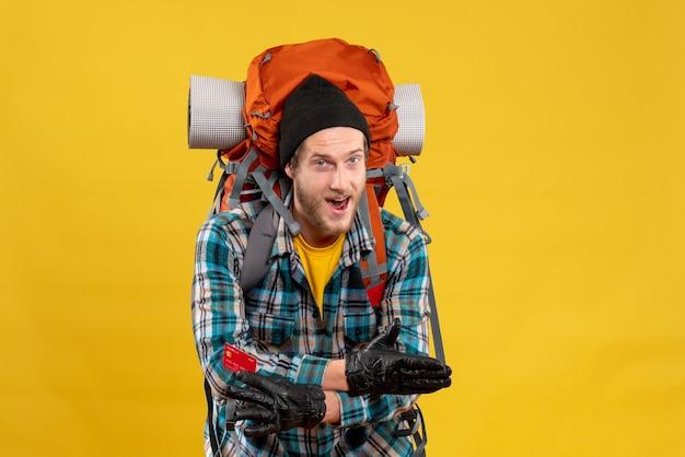 Vista frontale del giovane viaggiatore con zaino e sacco a pelo felice con la carta di credito della tenuta del cappello nero che dà la mano