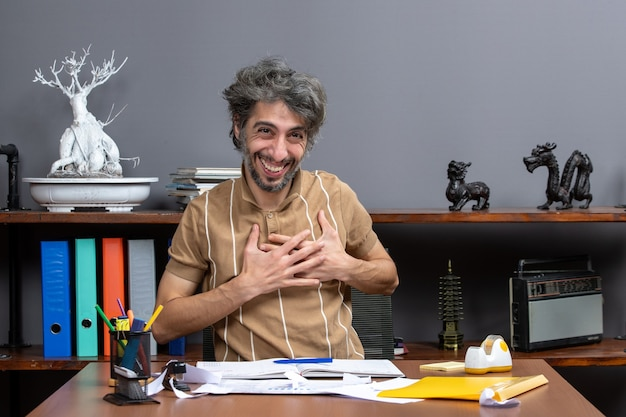 Front view happy young businessman sitting at desk in his office putting hand on his chest