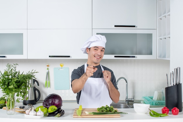 Front view happy young chef in uniform pointing at camera