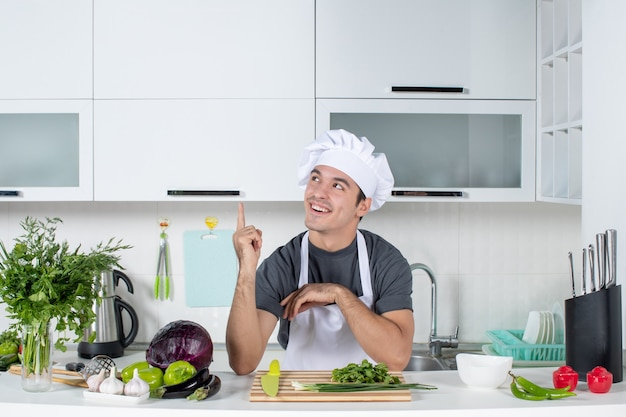 Front view happy young cook in uniform pointing at kitchen cupboard