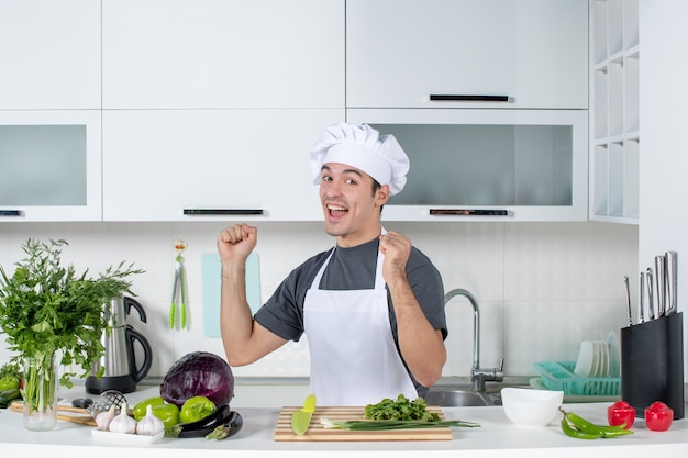 Front view happy young cook in uniform standing in kitchen