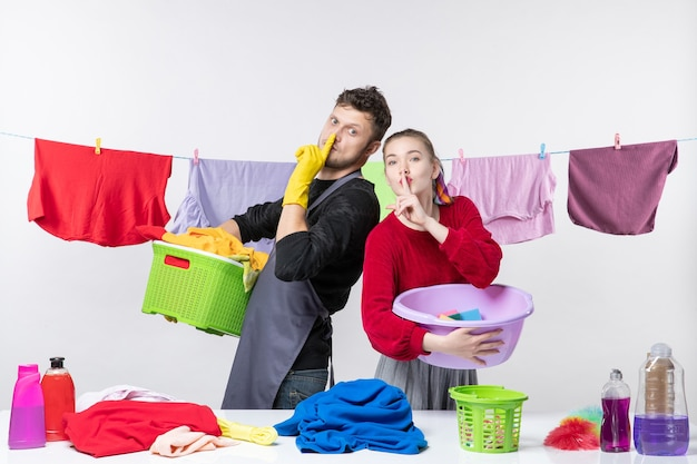 Front view of happy young couple making hush sign holding washing stuffs on white wall