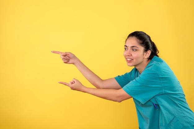 노란색 배경에 손가락 왼쪽 방향으로 가리키는 제복을 입은 전면보기 행복 한 젊은 여성 의사
