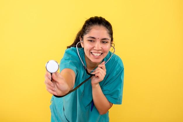 Medico femminile giovane felice di vista frontale con lo stetoscopio che sta su fondo giallo